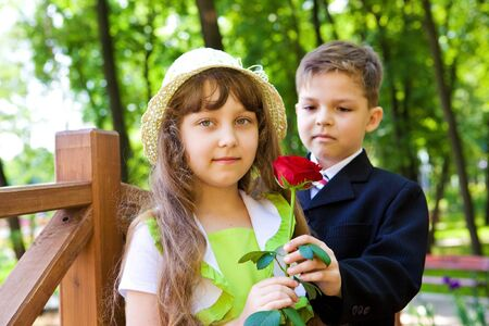 Preschool boy in suit giving a rose to the sweet girl photo