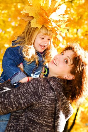 Happy mother and daughter in the autumn park photo
