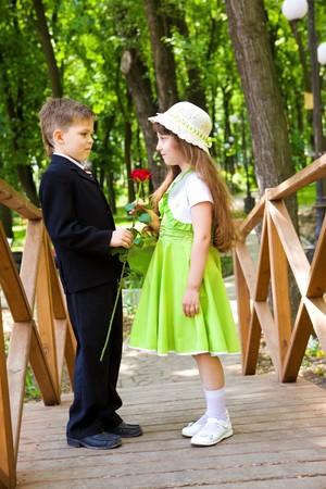 Preschool jongen in pak een roos te geven aan het lief meisje