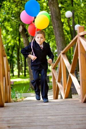 A happy kid with balloons running over the bridge photo