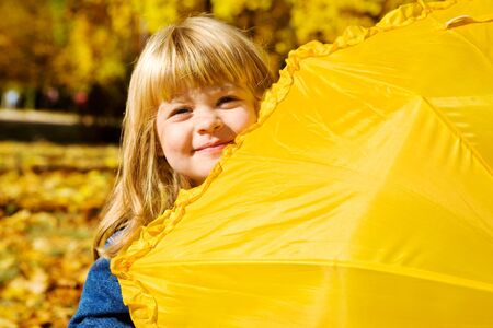 Sweet preschool girl hiding behind yellow umbrella photo