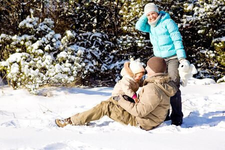 Happy attractive family playing in snow photo