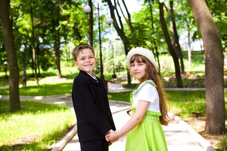 Preschool boy in suit and a sweet little lady holding hands Stock Photo - 7367480