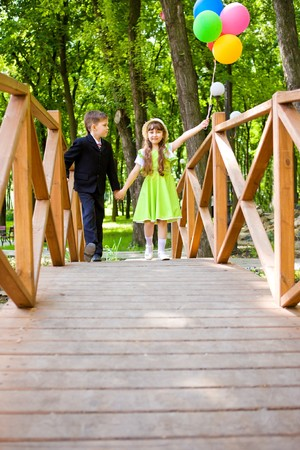 Preschool boy in suit and a lovely girl enjoying time together photo