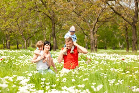 Beautiful happy family having fun on the meadow photo