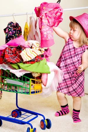 Cute blonde meisje kleding in winkel wagen plaatsen  Stockfoto