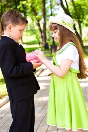 embarassed: Preschool boy in suit giving a present box to the sweet girl Stock Photo