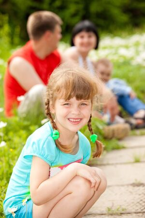 Lovely preschool girl in the outdoors, her family behind photo