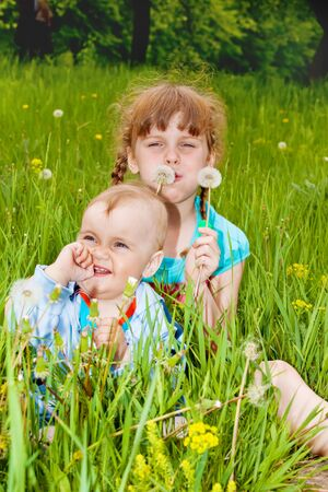 Two kids sitting in grass and blowing dandelion photo