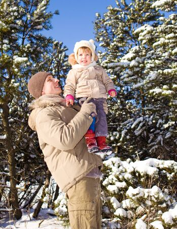 Dad playing with toddler girl in a winter park photo