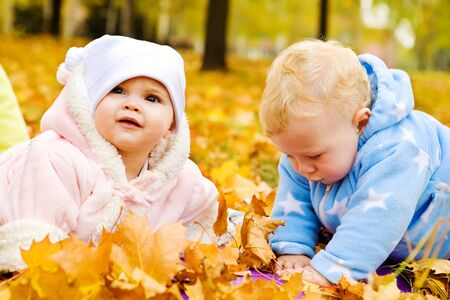 Lovely babies crawling in the autumn park photo