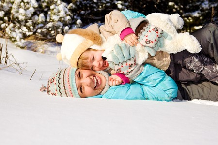 Happy mother and little girl lying in snow photo
