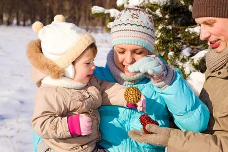 papa y mama: Mam�, pap� y su hija jugando con decoraci�n de Navidad  Foto de archivo