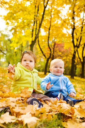 Two sweet kids sitting on the autumn leaves photo