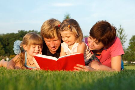 Sweet family reading a book on the green grass photo