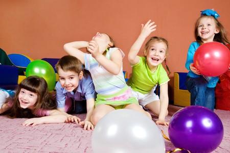 ni�as jugando: Ni�os de edad preescolares felices jugando con globos  Foto de archivo