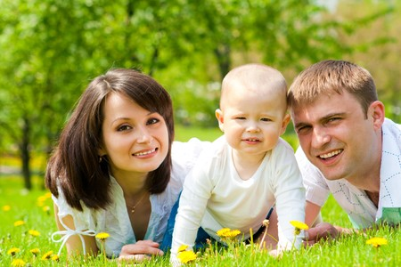 Mother, father and baby lying on grass photo