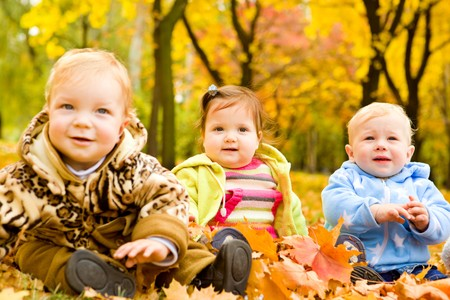 Three baby friends sitting in autumn park photo