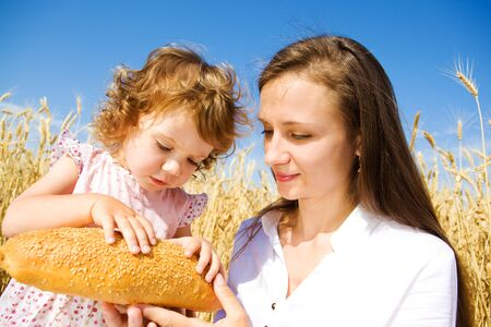 Toddler girl taking off seeds from bread photo