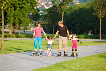 A happy family skating in a summer park photo