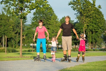 Parents and two daughters skating in a summer park Stock Photo - 7449418
