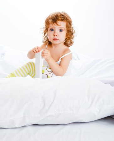 A cute girl in white sitting in bed Stock Photo - 7449367