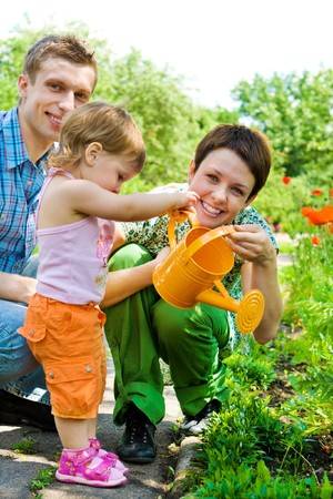Family watering flowers in the garden photo