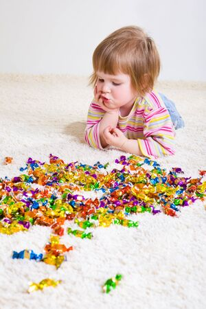 Sweet girl looking at candies and making choice photo