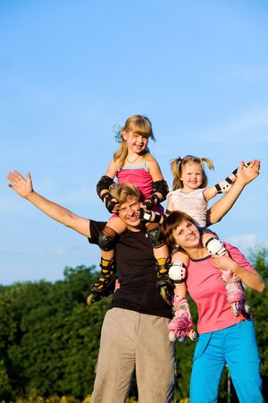Happy parents with kids in roller skates Stock Photo - 7498410