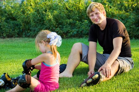 Father and daughter putting on roller skates photo