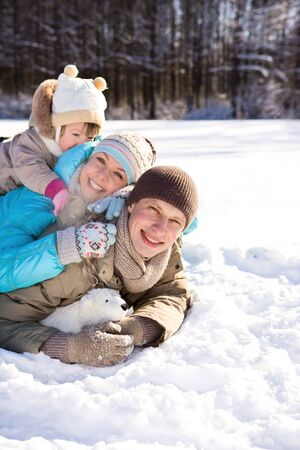 Happy young family enjoying their weekend in a winter park photo