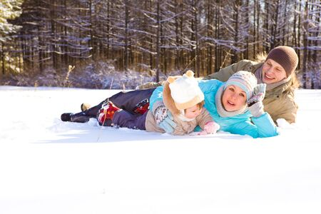 Attractive family having fun in a winter park photo