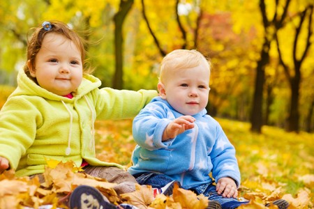 sister: Sweet kids sitting on the autumn leaves