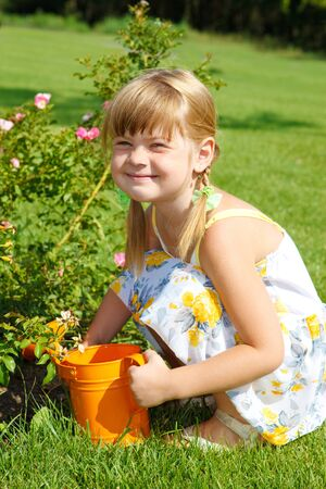 Preschool girl watering roses photo