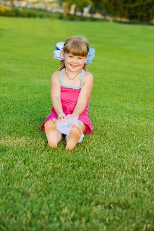 Preschool cutie sitting on the grass photo