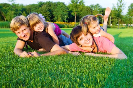 Sweet family playing  on the green grass photo