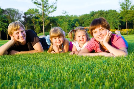 Parents with little daughters  on the green grass photo