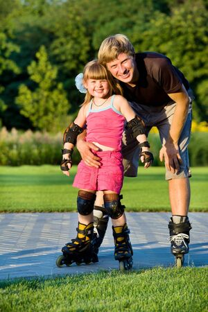 elbow pad: Dad and daughter rollerskating in park Stock Photo