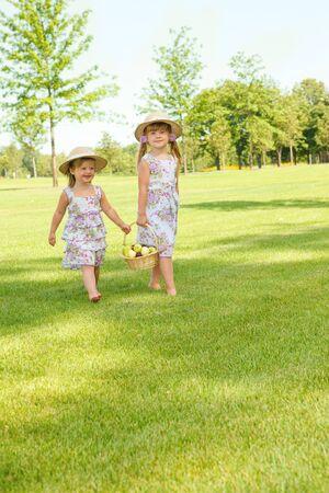 Two sweet kids in garden with fruit basket beside photo