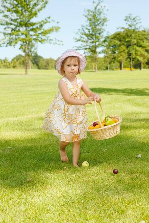 Lovely little girl carrying a fruit basket in garden Stock Photo - 7498723