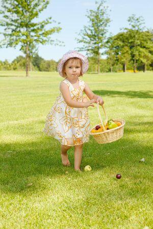 Lovely little girl carrying a fruit basket in garden Stock Photo - 7498723