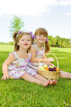 Two sweet kids in garden with fruit basket beside Stock Photo - 7498405