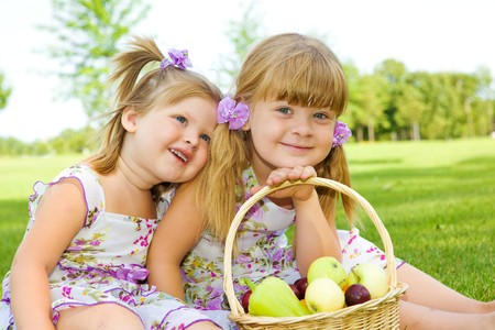Two sweet kids in garden with fruit basket beside Stock Photo - 7498602