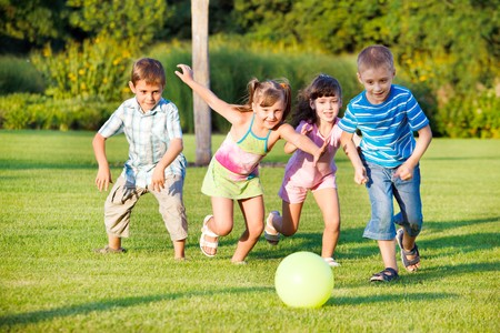 ni�os jugando en el parque: Ni�os y ni�as corriendo hacia la bola