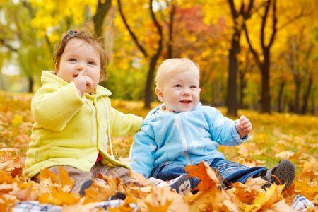 Sweet kids sitting on the autumn leaves photo