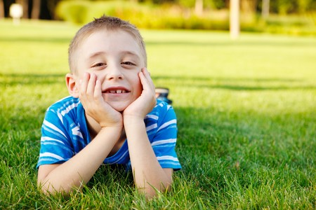 Boy lying on grass laughing photo