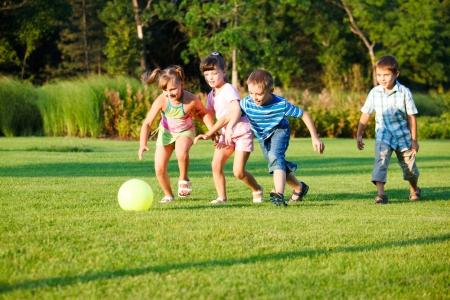 ni�os jugando en el parque: Ni�os jugando con la pelota  Foto de archivo