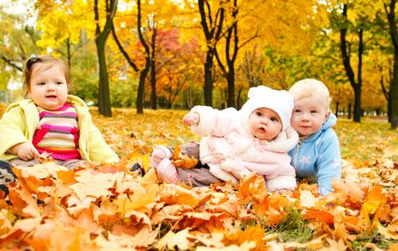 Kids sitting on ground covered with leaves photo