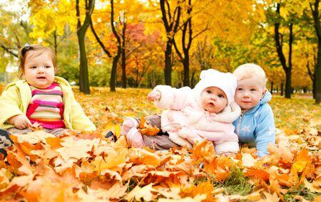 Kinder, die sitzen auf dem Boden bedeckt mit Blättern