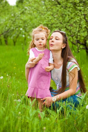 Mother and curly girl blowing dandelion away Stock Photo - 7640845